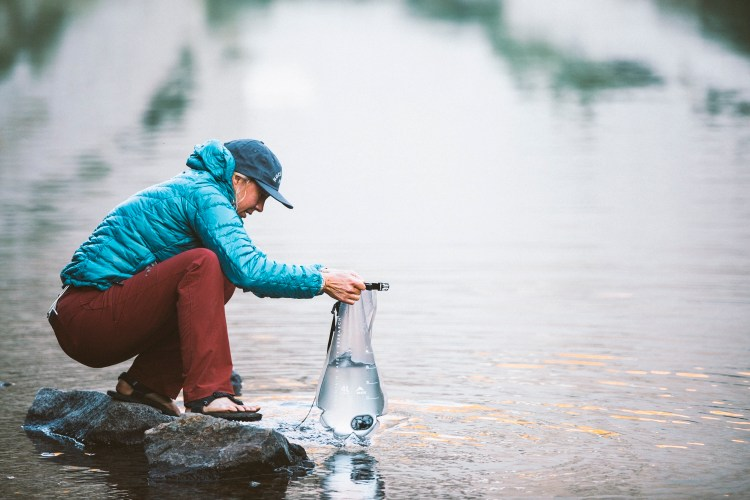 forest woodward photo of hiker filtering water from an alpine lake