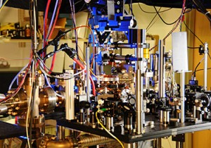 NIST's ultra-stable ytterbium lattice atomic clock. Ytterbium atoms are generated in an oven (large metal cylinder on the left) and sent to a vacuum chamber in the center of the photo to be manipulated and probed by lasers. Laser light is transported to the clock by five fibers (such as the yellow fiber in the lower center of the photo).  Credit: Burrus/NIST