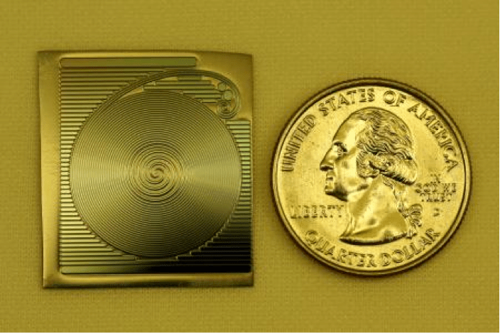 A photograph of the spiral chip-based optical resonator developed at Caltech, shown next to a quarter to provide scale. Credit: Hansuek Lee/Caltech