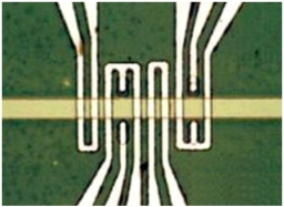 A picture of spin wave devices, showing magneto-electric cells used for voltage-controlled spin wave generation in the spin wave bus material (yellow stripe). The yellow stripe is about four micrometers in diameter. (Source: UCLA)