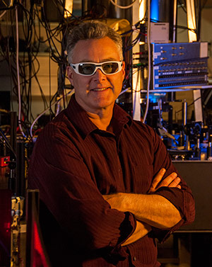 Physicist Andrew Wilson in a NIST quantum information laboratory. NIST researchers have demonstrated fine control of two ions confined in separate zones of an electric-field trap, which is chilled to low temperatures in the silver chamber behind Wilson. The techniques will be useful in simulating complex quantum systems such as high-temperature superconductors.