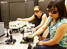 Purdue physics professor Yulia Pushkar (left) and postdoctoral researcher Lifen Yan work in Pushkar's laser lab. Pushkar and Yan are part of an international team using spinach to study the proteins involved in photosynthesis.  (Source: Purdue University)