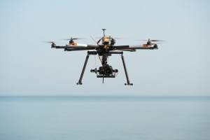 Radio control octocopter (Drone/ UAV) carrying SLR professional camera in the mid-air.