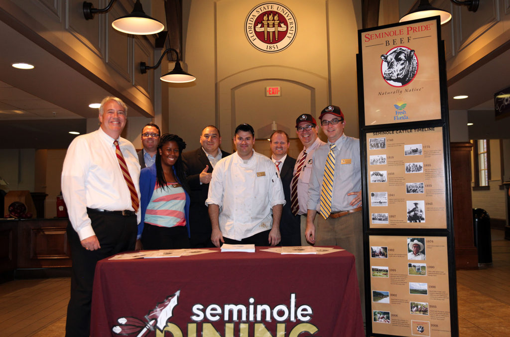 Seminole Pride Beef director of business development Michael Sauceda, thumbs up next to the chef, poses with members of the FSU food service department by the Seminole Pride Beef display in FSU's Suwannee Room dining hall during the special event that fed 900 people a grand meal of carved striploin steak Oct 14. (Beverly Bidney photo)