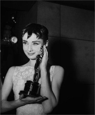 1954 --- Audrey Hepburn holding the Academy Award for best actress in Roman Holiday, her first American film. --- Image by © Bettmann/CORBIS