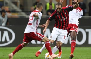 MILAN, ITALY - OCTOBER 04: Gonzalo Higuain (C) of AC Milan is challenged by Yaya Toure (R) and Guilherme (L) of Olympiacos during the UEFA Europa League Group F match between AC Milan and Olympiacos at Stadio Giuseppe Meazza on October 4, 2018 in Milan, Italy. (Photo by Marco Luzzani/Getty Images)