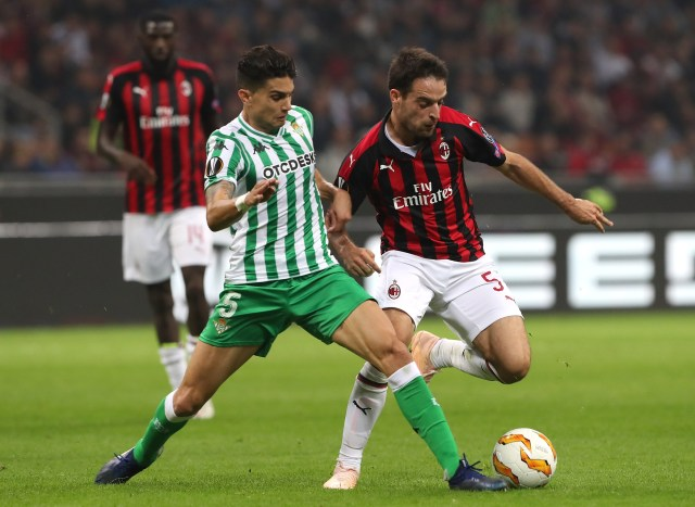 MILAN, ITALY - OCTOBER 25: Giacomo Bonaventura (R) of AC Milan competes for the ball with Marc Bartra (L) of Real Betis during the UEFA Europa League Group F match between AC Milan and Real Betis at Stadio Giuseppe Meazza on October 25, 2018 in Milan, Italy. (Photo by Marco Luzzani/Getty Images)