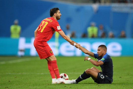 SAINT PETERSBURG, RUSSIA - JULY 10: Yannick Carrasco of Belgium helps Kylian Mbappe of France to his feet during the 2018 FIFA World Cup Russia Semi Final match between Belgium and France at Saint Petersburg Stadium on July 10, 2018 in Saint Petersburg, Russia. (Photo by Shaun Botterill/Getty Images)