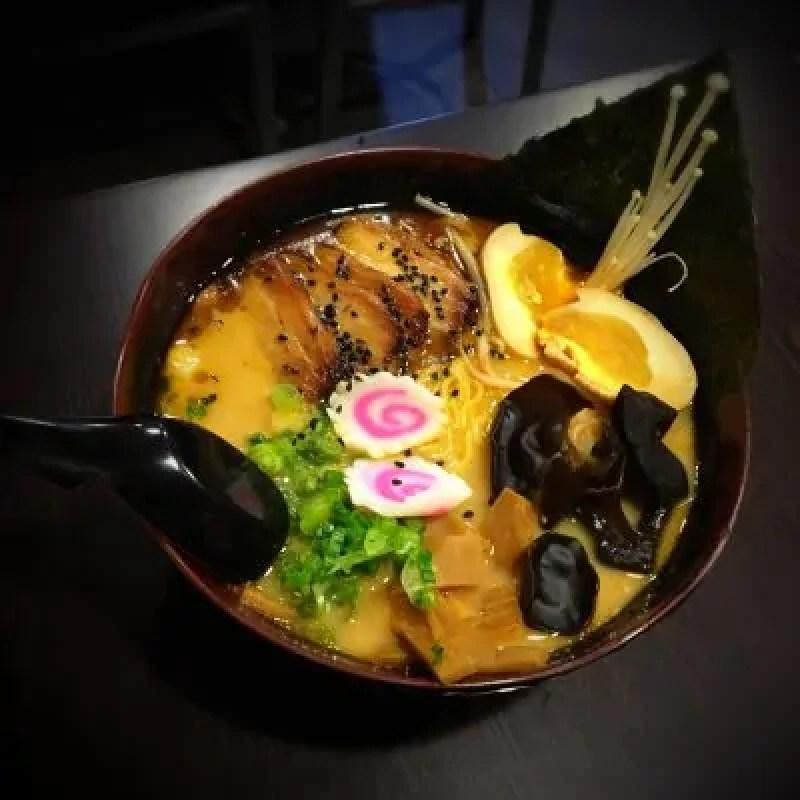 Un piatto di ramen con pasta, carne, verdura, uova, e germogli di soia