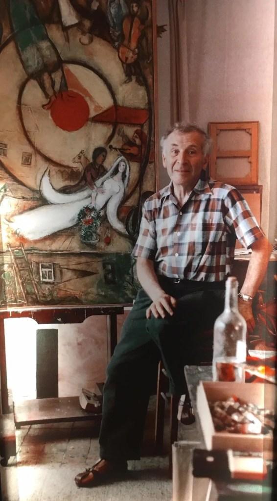 Marc Chagall con uno dei suoi dipinti sullo sfondo