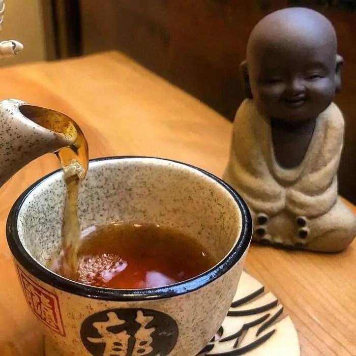 Tè giapponese in tazza con una statua