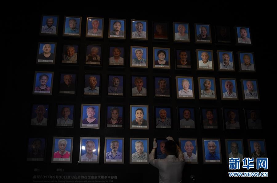 館内にある南京大虐殺生存者の写真の壁に掲げられた万秀英さんの写真の灯りが消される様子(撮影・季春鵬)。人民網より