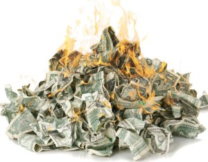 Screwed up dollar notes in a pile on fire