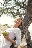 Portrait of a beautiful healthy senior tourist woman leaning on tree, relaxing by coast, eating a green apple on holiday, nature outdoors. Healthy fruit eating lifestyle, mature woman, sea exterior.