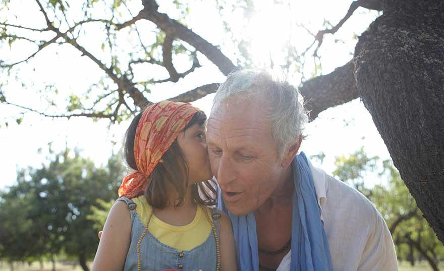 child-whispering-into-older-mans-ear