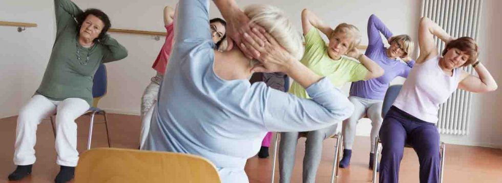 teacher and active senior women yoga class on chairs