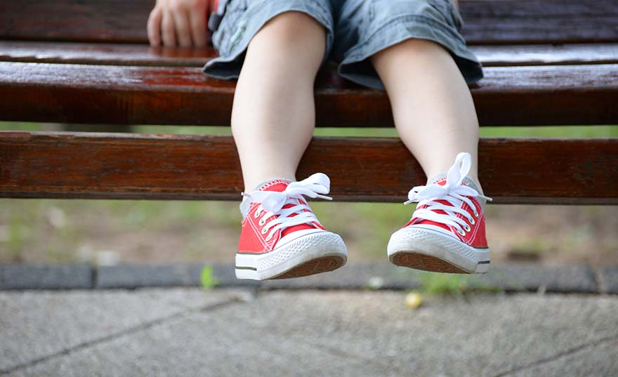 Child feet in red sneakers