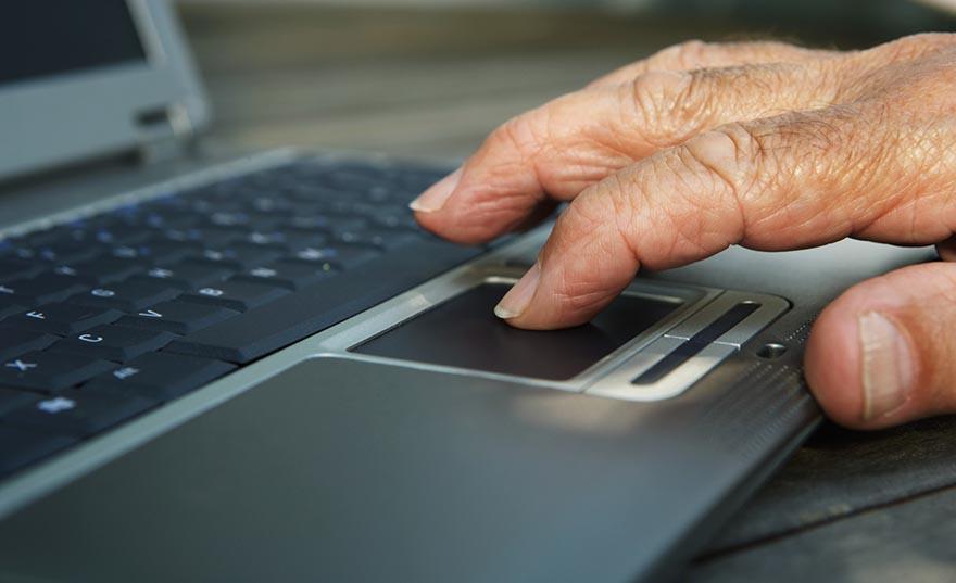 Senior man using laptop, close-up