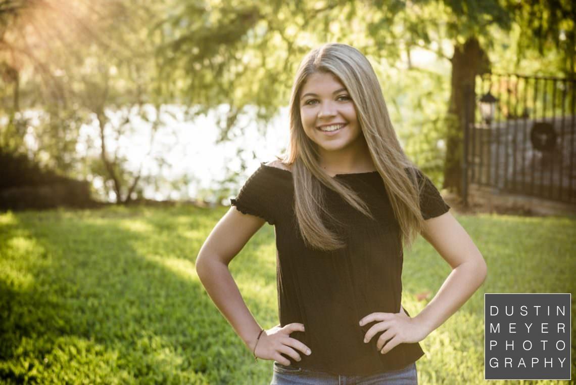 blonde girl senior portraits backlit sun flare flair black shirt smile