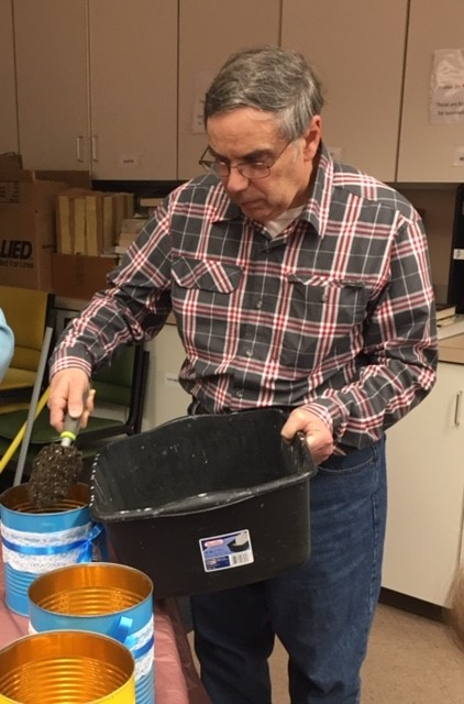Man scooping topsoil into a bucket