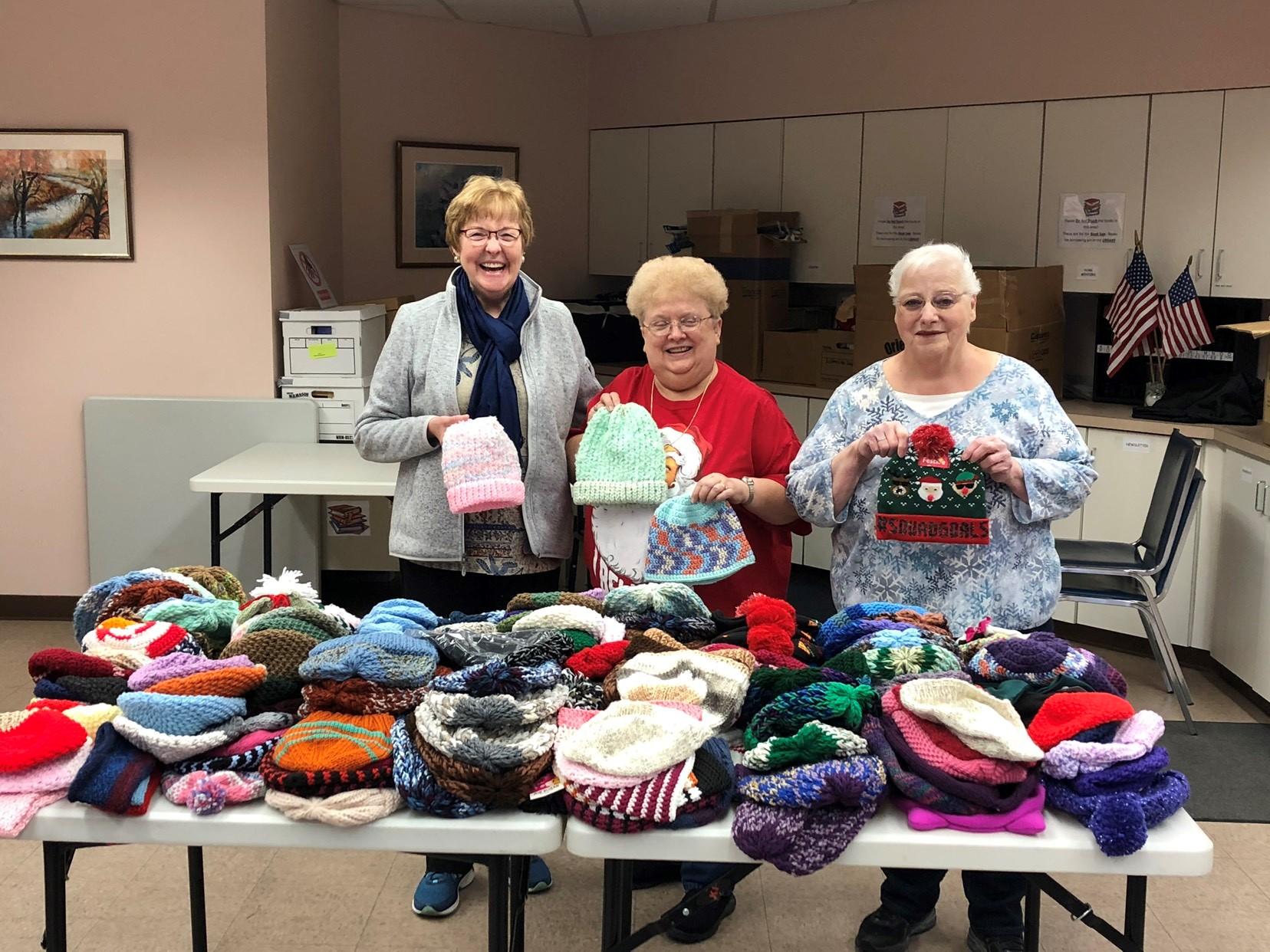 Women holding knit hats