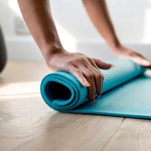 Women rolling up a yoga mat