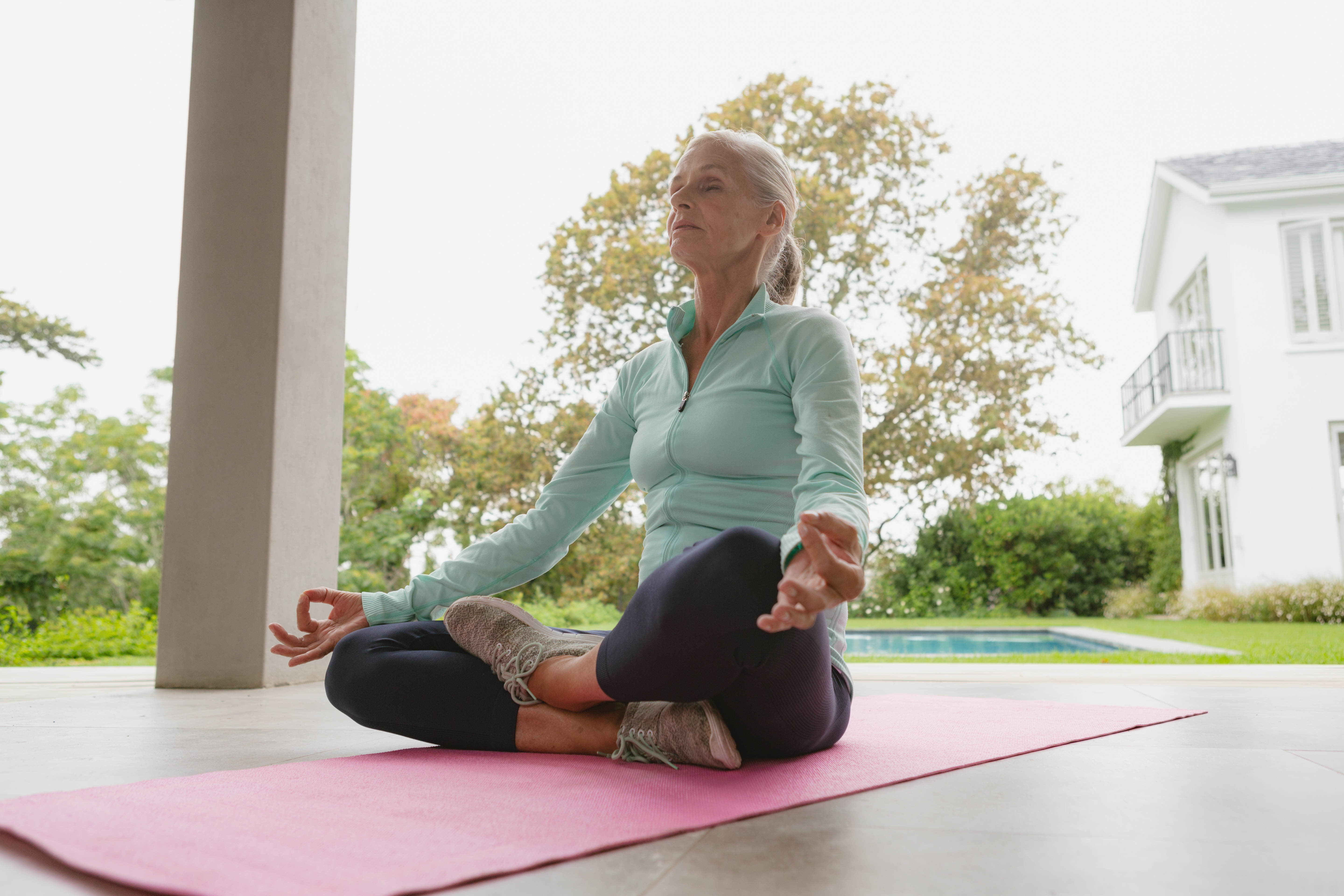 Low angle view of active senior Caucasian woman doing yoga on exercise mat in the porch at home