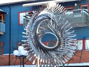 Närheten till vatten, genom kanalen intill, har varit vägledande för Ilhan Komans skulptur Vattenvirvel på Mälarö torg i Ekerö centrum. Skulpturen är utformad som en virvel.