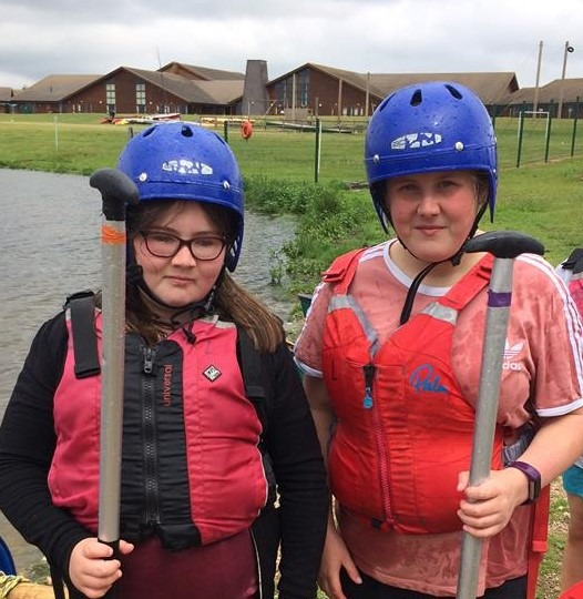 Two girls, wearing life jackets and blue helmets and carrying oars.