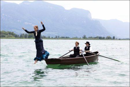 Eine Frau springt von einem Ruderboot bekleidet ins Wasser