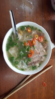 Sampling some traditional Vietnamese soup, otherwise known as pho.