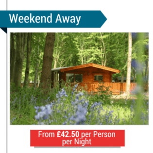 A Log Cabin In The Woods With The Text 'Weekend Away From £42.50 Per Person Per Night'