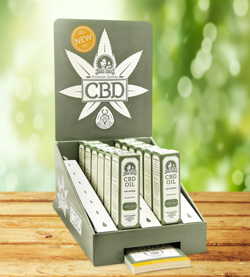 Photo of POS packaging for Sensi Seeds CBD oil on a wooden table against a blurred background. Inside, twelve individual packages containing CBD oil are visible. Under the POS packaging there is a pile of cards the size of business cards.