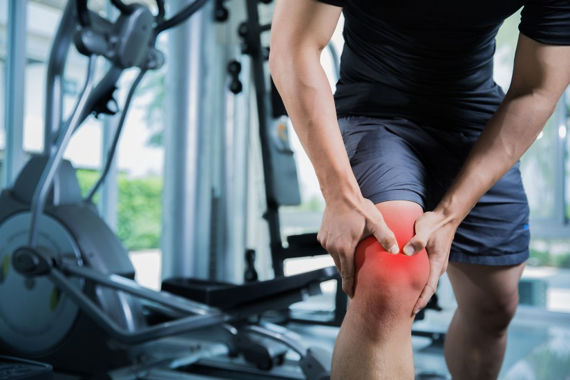 The photo shows the lower body of a man in a gym. The man's knee is red and he is holding it in both hands.