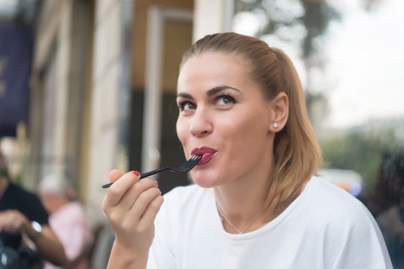 Portrait of a young woman looking up mischievously as she eats something with a fork. From the background, she appears to be sitting in a restaurant.