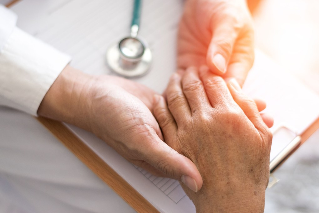 The photo shows the hand of an older person being touched by two other hands. The white sleeves and a stethoscope indicate that this is a medical examination.