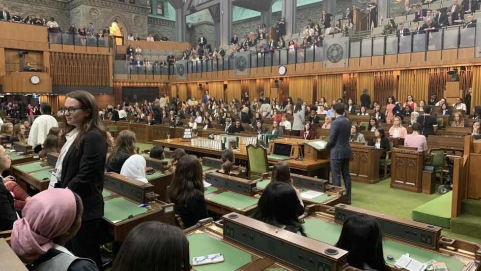 Une dizaine de femmes tournent le dos à Justin Trudeau, qui parle à la Chambre des communes. Des dizaines d'autres sont assises.