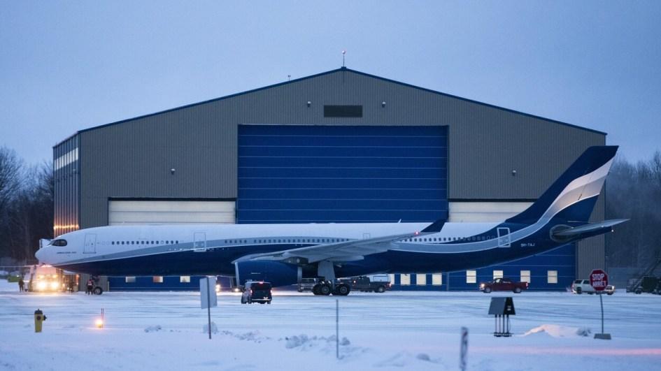 Un Airbus A330 devant un grand hangar.