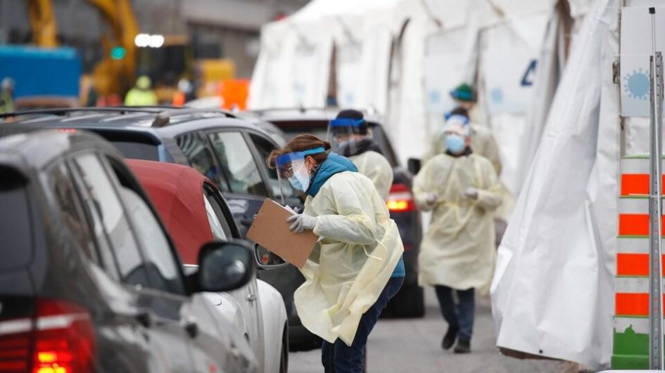 Des travailleuses de la santé, portant un masque, des gants et une visière, vont à la rencontre d'automobilistes à l'extérieur de la clinique de dépistage.