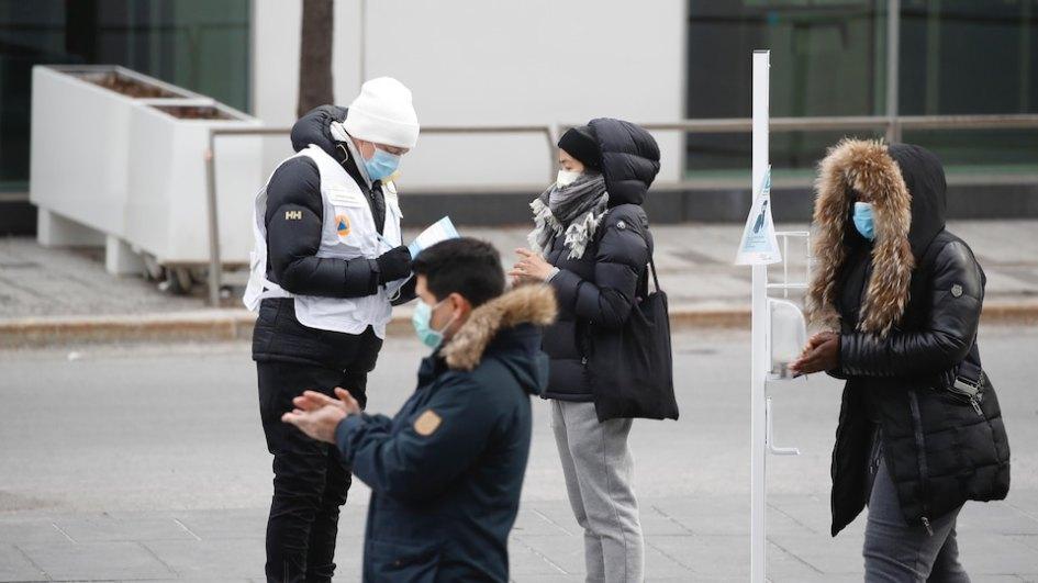 Trois personnes habillées chaudement et portant un masque désinfectent leurs mains en attendant d'être rencontrées par une employée de la clinique à l'extérieur.