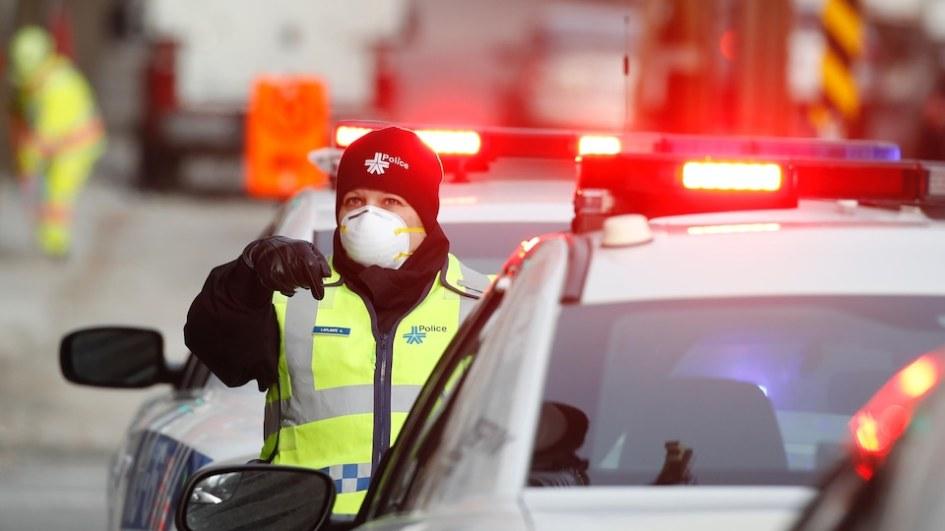Un policier masqué debout près de plusieurs auto-patrouilles avec les gyrophares allumés.