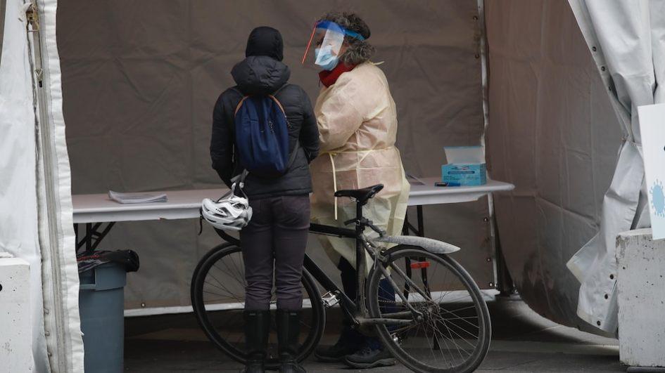 Une cycliste discute avec une travailleuse de la santé dans une tente extérieure.