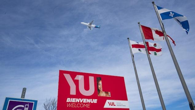 Des drapeaux, une grande pancarte sur laquelle il est écrit YUL, et un avion dans le ciel.