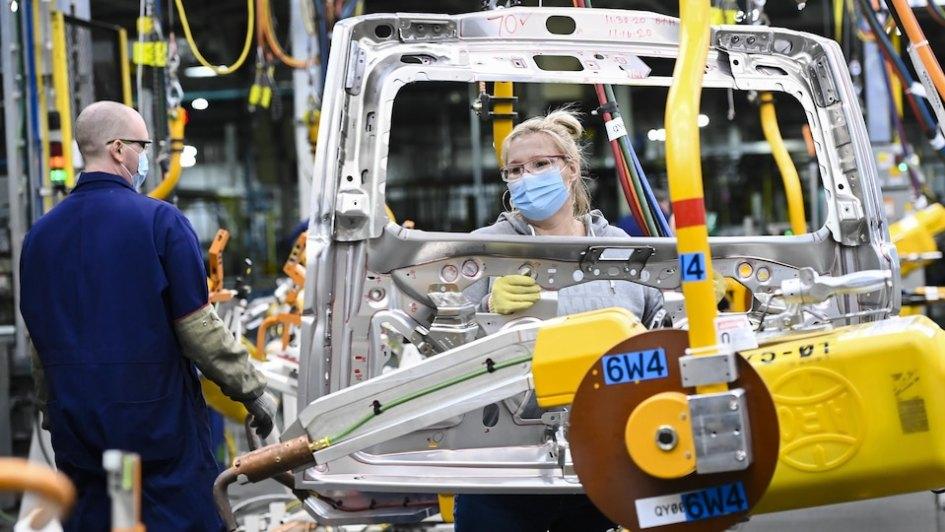 Deux travailleurs dans une usine de GM portent un masque de protection.