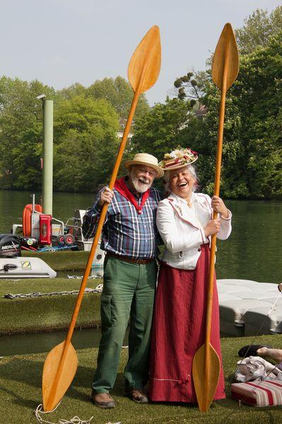 Un homme au canotier et une Dame costumée 1900 posent avec deux pagayes verticales