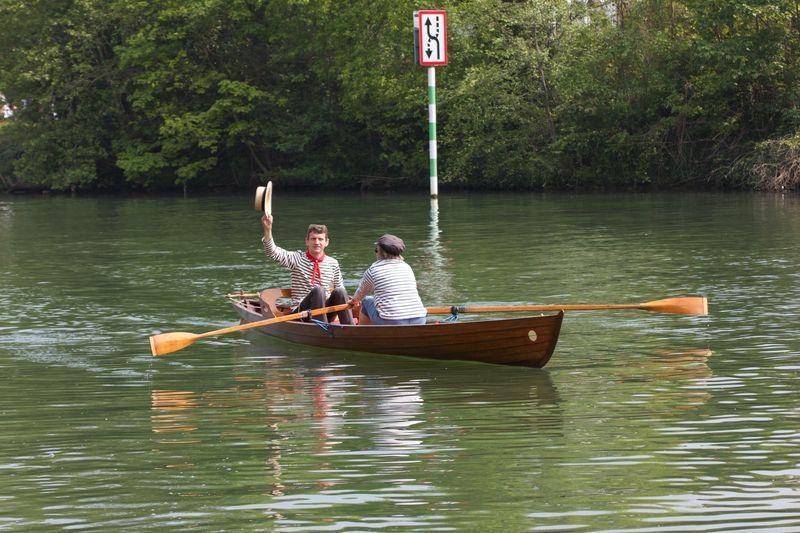 La yole Lutin sur l'eau ; le barrreur salue, la rameuse lui fait face