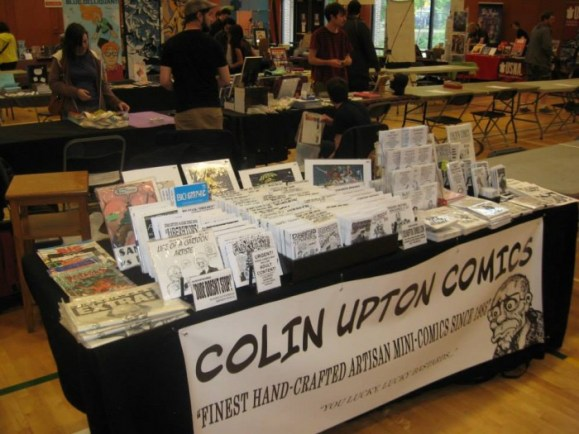 "Colin's table at Vancaf 2014  The banner reads: "" Colin Upton Comics"" ""Finest hand-crafted artisan mini-comics since 1985"" ""You lucky, lucky bastards"""