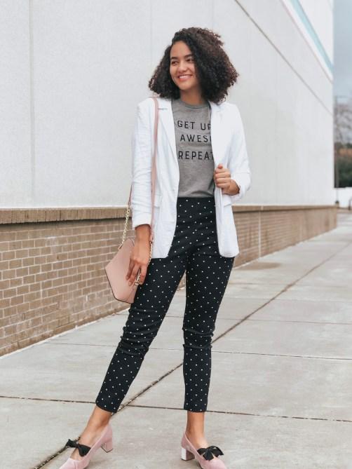 White blazer, black polka dot pants, gray graphic tee, pink velvet block heels, curly hair girl.