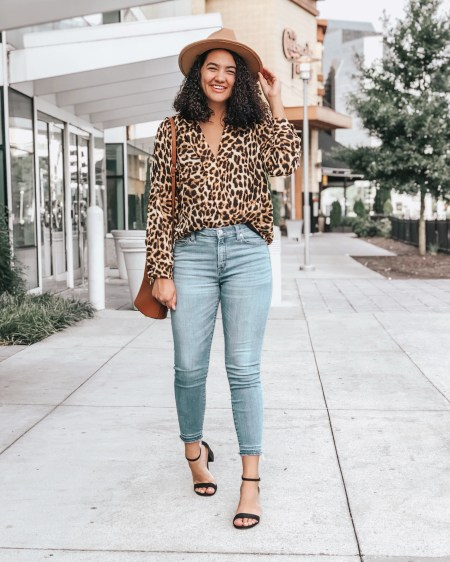 Girl with curly hair wearing a leopard print blouse, a pair of raw hem jeans, black block heels, a cognac colored crossbody bag, and a brown fedora from amazon under $20.