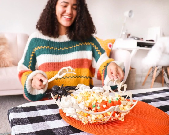 Girl in a fall sweater serving candy from a skeleton bowl with skeleton tongs